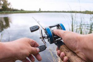 Man using a baitcasting reel at a lake.