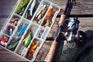 Tacklebox with bass lures and a spinning rod and reel