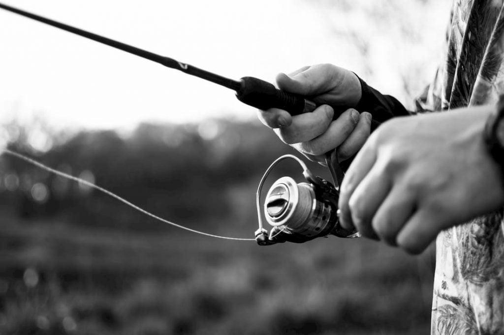 Close up shot on man retrieving fishing line.