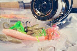 Fishing reel next to jigs and trailers.