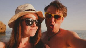 Woman and man posing on beach wearing sunglasses